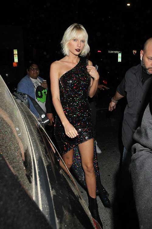 taylor chegando na festa com cabelo platinado e vestido diferente