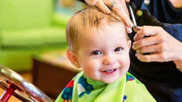 bebe se divertindo ao cortar cabelo pela primeira vez