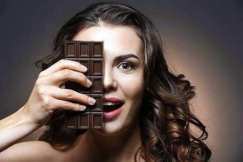 foto de mulher segurando chocolate perto do cabelo