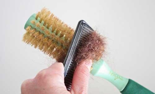 foto de escova de cabelo cheia de fios presos