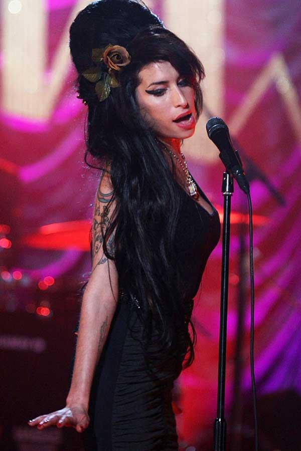 amy Winehouse com seu clássico penteado beehive enfeitado com flores
